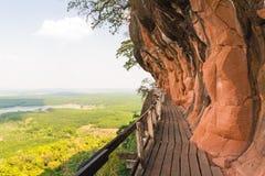 Mooie Houten brug in rode cliffside bij de berg van Wat Phu tok royalty-vrije stock foto