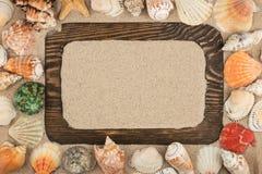Mooie houten kader, sterren en zeeschelpen op de zandachtergrond, met plaats voor uw beeld, tekst royalty-vrije stock afbeelding