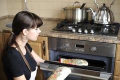 Mooie huisvrouw die de oven gebruikt stock fotografie