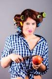 Mooie huisvrouw die met krulspelden appel en het mes houden Royalty-vrije Stock Afbeelding