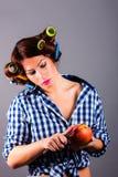 Mooie huisvrouw die met krulspelden appel en het mes houdt Stock Foto
