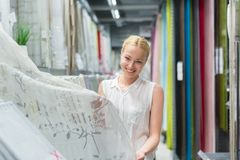 Mooie huisvrouw die witte gordijnen in het meubilairopslag van het huisdecor kopen stock afbeeldingen