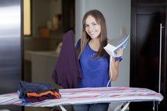 Mooie huisvrouw het strijken kleren Stock Foto's