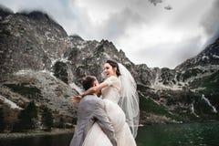 Mooie huwelijksphotosession De bruidegom omcirkelt zijn jonge bruid, op de kust van het meer Morskie Oko polen stock afbeeldingen