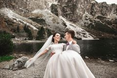 Mooie huwelijksphotosession De bruidegom omcirkelt zijn jonge bruid, op de kust van het meer Morskie Oko polen royalty-vrije stock fotografie