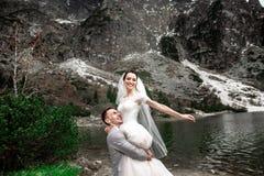 Mooie huwelijksphotosession De bruidegom omcirkelt zijn jonge bruid, op de kust van het meer Morskie Oko polen stock fotografie