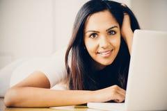 Mooie Indische studente die laptop computer thuis met behulp van Royalty-vrije Stock Foto's