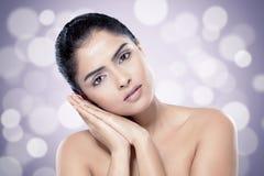Mooie Indische vrouw met gezonde huid tegen vage lichtenachtergrond stock afbeelding