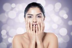 Mooie Indische vrouw met gezonde huid tegen vage lichtenachtergrond stock fotografie