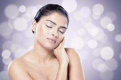 Mooie Indische vrouw met gezonde huid tegen vage lichtenachtergrond royalty-vrije stock afbeeldingen
