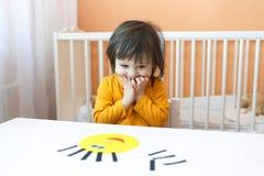 Mooie 2 jaar kind gemaakt gezichts van document details Stock Fotografie