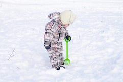 Mooie 1 jaarbaby met schop in de winter Stock Afbeelding