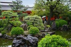 Mooie Japanse tuin met kleurrijke esdoornbomen en meer in de herfst, toeristen die in regenachtige dag Kyoto Japan waiking stock foto