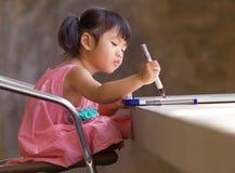 Mooie jong geitjepraktijk voor het schrijven op witte breed vóór lear klasse royalty-vrije stock afbeeldingen