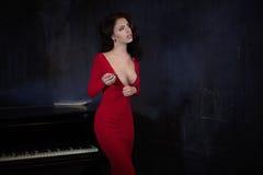 Mooie jonge aantrekkelijke vrouw in avond rode kleding en piano stock foto