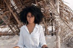 Mooie jonge Afrikaanse Amerikaanse meisjeszitting op zand bij bea Royalty-vrije Stock Foto's