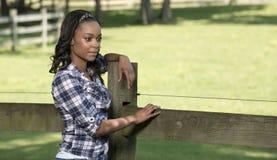 Mooie jonge Afrikaanse Amerikaanse vrouw die zich langs landelijke landbouwbedrijfomheining bevinden - Stock Foto's