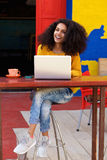 Mooie jonge Afrikaanse damezitting bij koffiewinkel met laptop Royalty-vrije Stock Fotografie