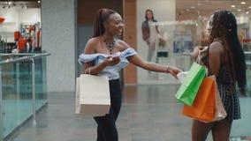 Mooie jonge Afrikaanse vrouwen die bij de opslag winkelen stock video