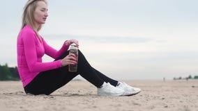 Mooie jonge atletische vrouw die na opleiding op het strand rusten Drinkt water van een plastic fles stock video