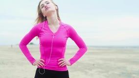 Mooie jonge atletische vrouw die oefening met hoofddraaien doen Het uitrekken van de halsspieren alvorens op te leiden stock video
