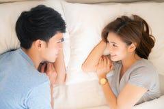 Mooie jonge Aziatische paarliefde die ogen samen op bed in de slaapkamer kijken royalty-vrije stock foto
