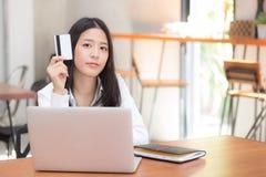 Mooie jonge Aziatische vrouw die een creditcard houden en online met het gebruiken van laptop computer bij koffie winkelen Stock Fotografie