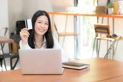 Mooie jonge Aziatische vrouw die een creditcard houden en online met het gebruiken van laptop computer winkelen Royalty-vrije Stock Fotografie
