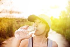 Mooie jonge Aziatische vrouw die in het park, de fles van het Holdingswater ter beschikking uitoefenen Het ontspannen op de weg royalty-vrije stock afbeelding