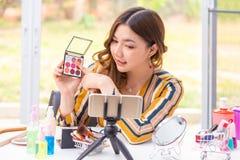 Mooie jonge Aziatische vrouw die online productoverzicht thuis maakt stock foto