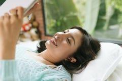 Mooie jonge Aziatische vrouw die op bed leggen en een agenda schrijven stock foto's