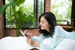Mooie jonge Aziatische vrouw die op bed leggen en een agenda schrijven stock fotografie