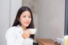 Mooie jonge Aziatische vrouw het drinken koffie en glimlach in de ochtend bij koffie Stock Afbeeldingen