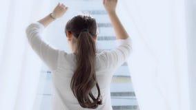 Mooie jonge Aziatische vrouw met gelukkige open gordijnen en rek lui bij het venster na kielzog op ochtend in de slaapkamer stock footage