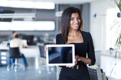 Mooie, jonge bedrijfsdame in de zwarte sterke tablet van de reeksgreep Stock Foto's