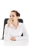Mooie jonge bedrijfsvrouw die een appel eten. Royalty-vrije Stock Afbeeldingen