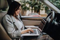 Mooie jonge bedrijfsvrouw die laptop in de auto met behulp van royalty-vrije stock foto