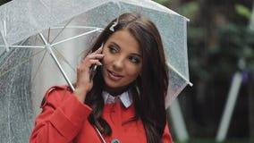 Mooie jonge bedrijfsvrouw die op smartphone op de straat in regenachtig weer, het glimlachen spreken, die paraplu houden en stock video