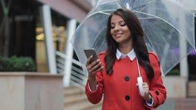 Mooie jonge bedrijfsvrouw die smartphone gebruiken die op de straat in regenachtig weer, het glimlachen lopen, die paraplu houden stock footage