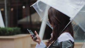 Mooie jonge bedrijfsvrouw die smartphone gebruiken die op de straat in regenachtig weer, het glimlachen lopen, die paraplu houden stock video
