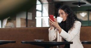 Mooie jonge bedrijfsvrouw in roze kostuum gebruikend smartphone en drinkend koffie op comfortabele koffie of modern kantoor stock videobeelden