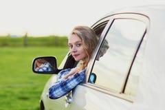 Mooie jonge bestuurder die uit de auto kijken Stock Foto's