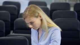 Mooie jonge blonde eerbiedige vrouw met tegenzin of niet slaand achtergrond van bureaustoelen stock videobeelden