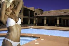 Mooie jonge blonde vrouw bij de pool van het toevluchthotel stock foto