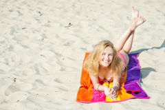 Mooie jonge blonde vrouw die op een strand liggen royalty-vrije stock fotografie