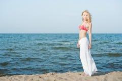 Mooie jonge blonde vrouw die op een strand lopen stock foto
