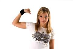 Mooie jonge blonde vrouw in een T-stukoverhemd dat een spier maakt stock afbeelding