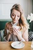 Mooie jonge blonde vrouw in een witte kleding die koffie van cappuccino met schuim genieten Royalty-vrije Stock Foto's