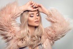 Mooie jonge blonde vrouw in roze bont caot De wintermanier Schoonheid Sexy ModelGirl met lang krullend glanzend haar en samenstel royalty-vrije stock fotografie