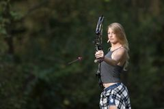 Mooie jonge blonde vrouwelijke schutter met samenstellingsboog stock foto